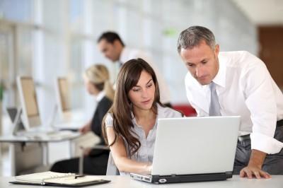 supervisor checking work of female worker